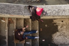 Near Ponte Regina Margherita. A drug addict shooting up with eroine on the stairs leading to the river bank.